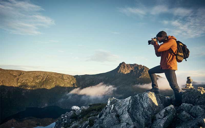 Outdoor photographer taking photo in mountains