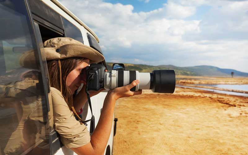 A lady is taking photos from the car
